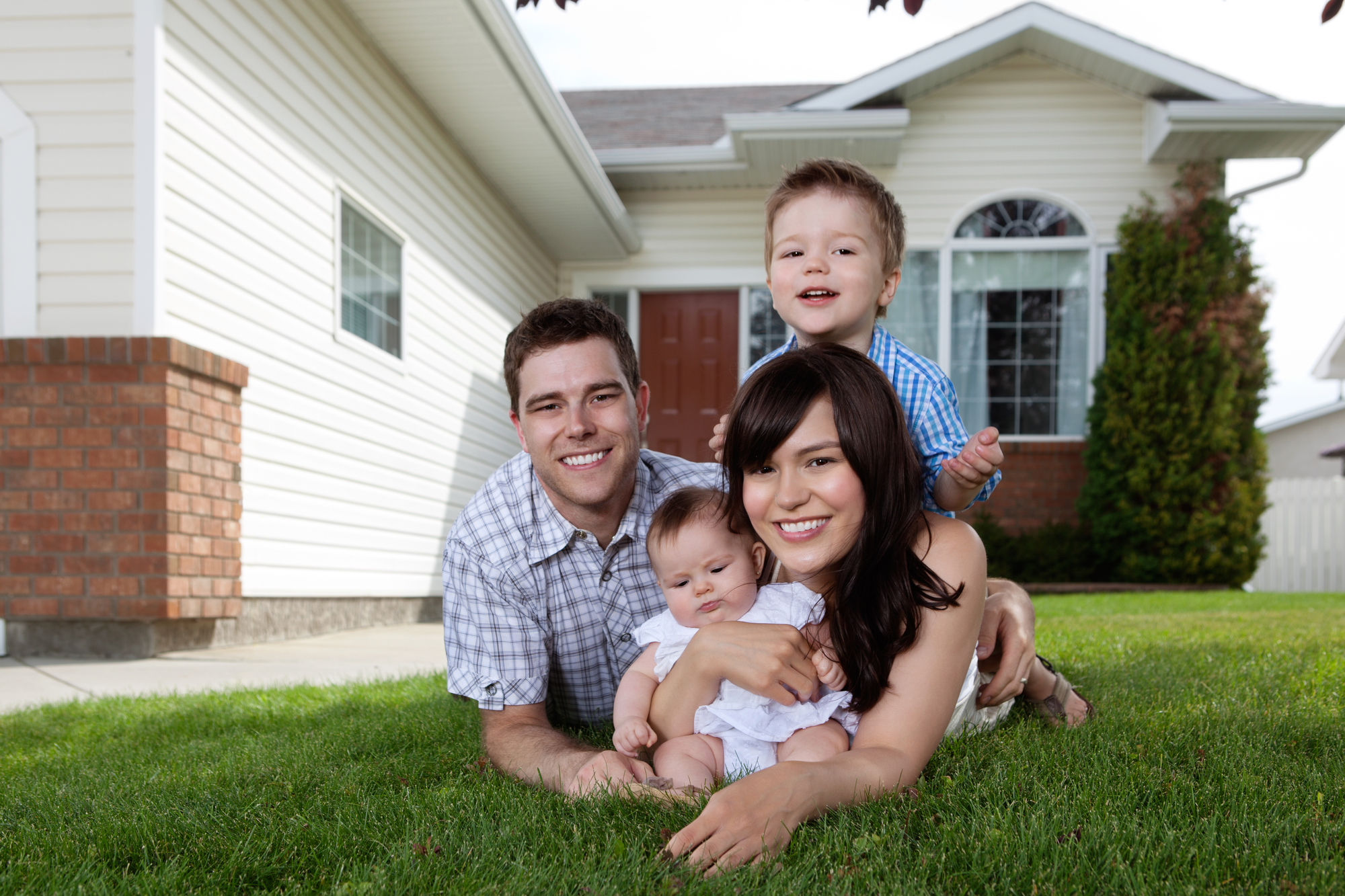 Family Laying in Grass in Front of Home with Homeowners Insurance in Santa Maria, CA