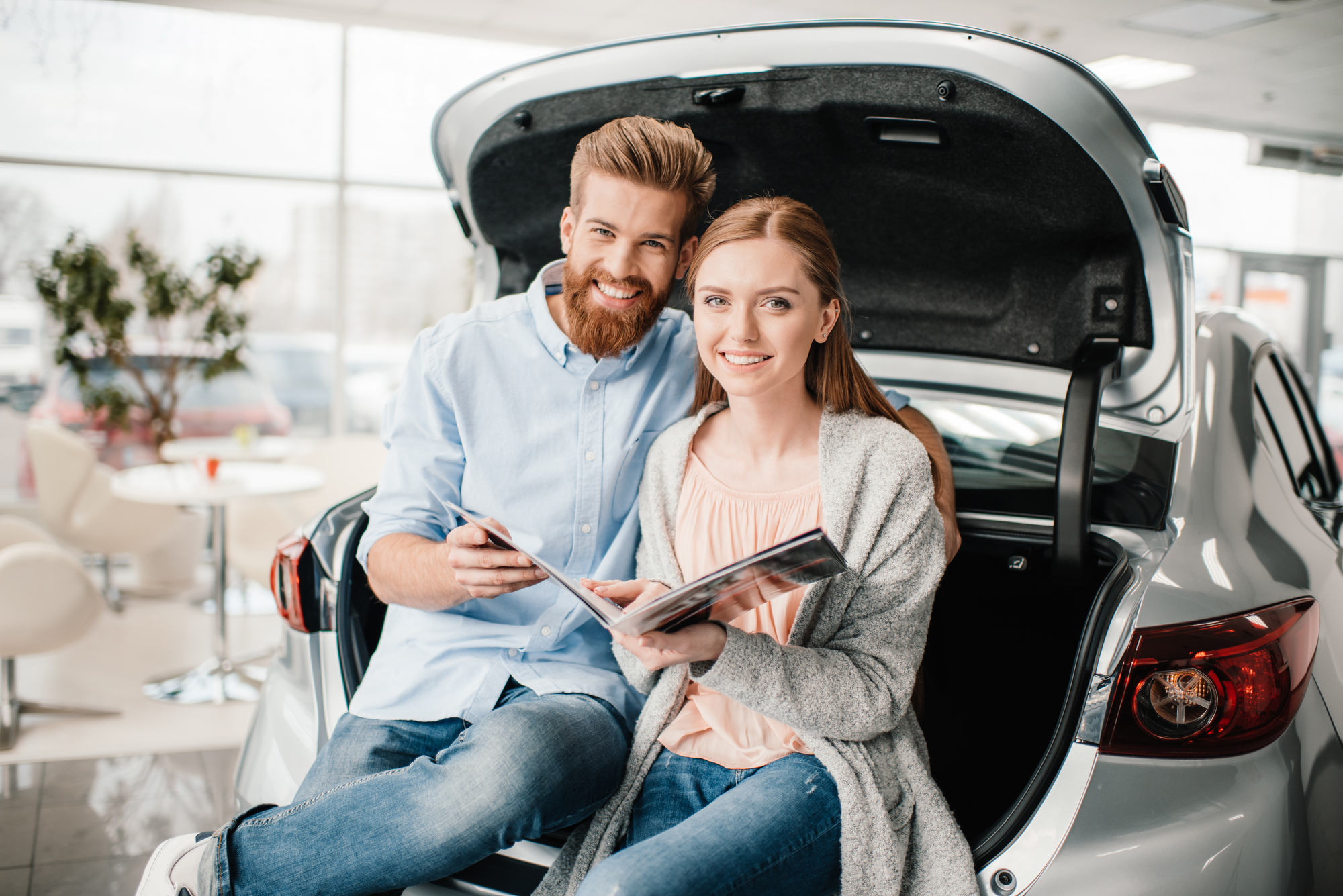 Couple Sitting on Truck of Car in Dealership with Auto Insurance in Santa Maria, CA
